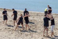 Un treno di due ragazze è impegnato nel lottare sulla spiaggia Immagini Stock Libere da Diritti