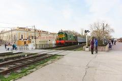 Un treno passeggeri con una locomotiva elettrica verde arriva alla stazione Pedone che attraversa la linea ferroviaria immagine stock libera da diritti
