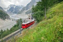 Un treno rosso in alpi francesi Fotografia Stock