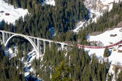 Un treno rosso che attraversa un ponte nelle alpi svizzere Fotografie Stock Libere da Diritti