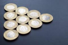 Un triángulo del polaco dos monedas del zloty en fondo mate oscuro gastado fotografía de archivo