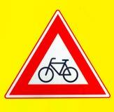 Un triangolo rosso si guarda da del segnale di pericolo dei ciclisti su un fondo giallo immagine stock