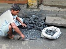 Un triturador masculino del carbón que rompe el carbón con el martillo Imagen de archivo