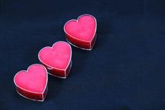 Un trío de corazones rosados en un fondo negro Imagen de archivo