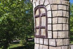 Un tronc d'arbre avec une fenêtre photo libre de droits