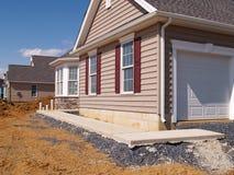 Un trottoir neuf par une construction à la maison image stock