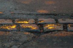Un trottoir s'est baigné en or, pavé rond gris couvert de gouttelettes de pluie qui reflètent le Sun image stock