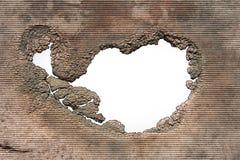 Un trou avec les bords de décomposition déchiquetés Photos stock