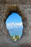 Un trou dans le mur de la grotte di Catullo avec vue sur le lac photos libres de droits