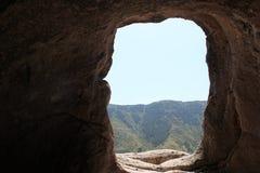 Un trou dans une montagne avec une vue Photo stock