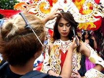 Un truccatore stende il trucco su partecipante di parata al suo costume variopinto durante il festival di Sumaka nella città di A Immagine Stock Libera da Diritti