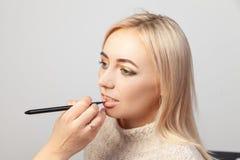 Un trucco in uno studio di bellezza, un truccatore con una spazzola in sua mano mette un prodotto sulla bocca di un modello biond immagini stock