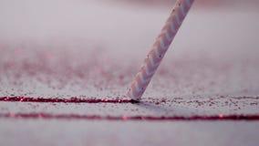 Un tube blanc-rose suce une ligne d'un miroitement rouge banque de vidéos
