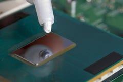 Un tubo di grasso termico sopra il chip di unità di elaborazione immagine stock
