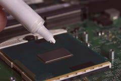 Un tubo di grasso termico sopra il chip di unit? di elaborazione immagini stock libere da diritti