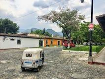 Un tuk de tuk sur les rues de pavé rond de l'Antigua, Guatemala photographie stock libre de droits