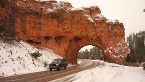 Un tunnel è tagliato attraverso la roccia rossa del canyon sulla strada principale 12 nell'Utah archivi video