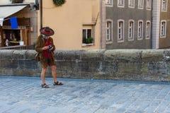 Un turista anziano su una pavimentazione del ciottolo con una macchina fotografica e nei vestiti bavaresi nazionali immagini stock
