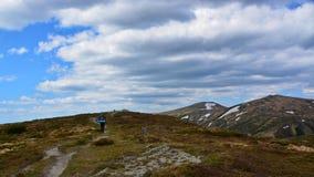 Un turista cammina lungo una pista nei precedenti delle montagne e delle nuvole Immagine Stock Libera da Diritti