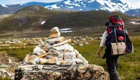 Un turista che passa una pietra miliare su una traccia di montagna Fotografia Stock Libera da Diritti