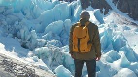 Un turista con una mochila amarilla mira el glaciar de Svartisen en Noruega almacen de video