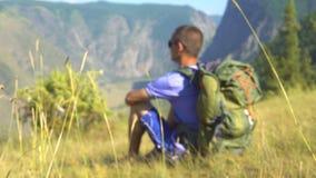 Un turista con una mochila en las montañas almacen de video