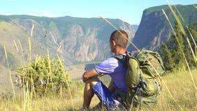 Un turista con una mochila en las montañas almacen de metraje de vídeo