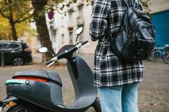 Un turista con una mochila va a utilizar una vespa eléctrica con una aplicación móvil en el teléfono y distal fotos de archivo libres de regalías