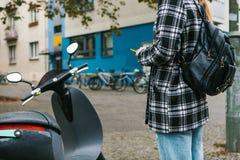Un turista con una mochila va a utilizar una vespa eléctrica con una aplicación móvil en el teléfono y distal fotografía de archivo