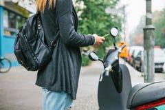 Un turista con una mochila va a utilizar una vespa eléctrica con una aplicación móvil en el teléfono y distal imagenes de archivo