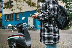 Un turista con una mochila va a utilizar una vespa eléctrica con una aplicación móvil en el teléfono y distal foto de archivo libre de regalías