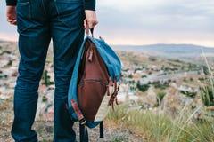 Un turista da un'altezza esamina il tramonto sopra una città della montagna Concetto di turismo, facente un'escursione backpacker fotografia stock