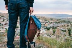 Un turista da un'altezza esamina il tramonto sopra una città della montagna Concetto di turismo, facente un'escursione backpacker immagine stock