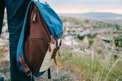 Un turista da un'altezza esamina il tramonto sopra una città della montagna Concetto di turismo, facente un'escursione backpacker immagine stock libera da diritti
