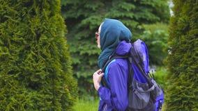 Un turista de la muchacha en un pañuelo y gafas de sol con una mochila que caminan en el parque almacen de video