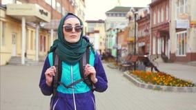 Un turista de la muchacha en un pañuelo y gafas de sol en una mochila que caminan abajo de la calle almacen de metraje de vídeo