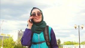 Un turista de la muchacha en un pañuelo y gafas de sol en una mochila que hablan en el teléfono almacen de video