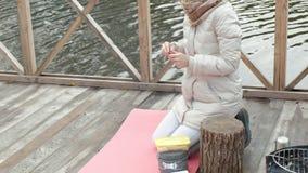 Un turista de la mujer se sienta en el puente cerca de la orilla del río, alimenta el perro, cocina la comida, comida campestre,  metrajes