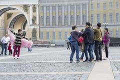 Un turista della donna dell'aspetto orientale che posa per un gruppo di compatrioti sul quadrato del palazzo di St Petersburg, Ru immagini stock