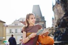 Un turista della donna nel centro di Praga con una mappa nelle mani di Fotografia Stock