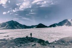 Un turista della montagna esamina il ghiacciaio davanti alla sua salita difficile a nonte Elbrus Immagini Stock