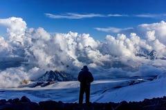 Un turista della montagna guarda pieno d'ammirazione la natura prima della sua ascesa difficile a nonte Elbrus Fotografia Stock