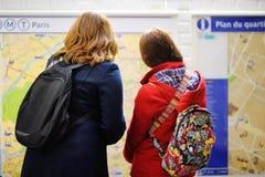 Un turista di due femmine che esamina la mappa della metropolitana fotografie stock