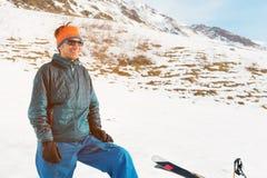 Un turista en abajo una chaqueta y gafas de sol con los guantes se coloca en las montañas del Cáucaso al lado de los esquís y Fotografía de archivo libre de regalías