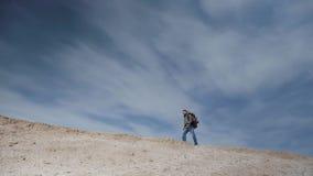 Un turista en los vidrios para la vista con una mochila grande camina a lo largo de un montón de la arena en el fondo de un cielo almacen de video