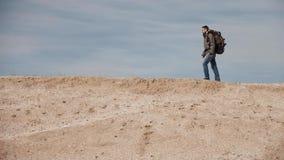 Un turista en los vidrios para la vista con una mochila grande camina a lo largo de un montón de la arena en el fondo de un cielo metrajes