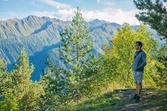 Un turista en pantalones cortos y una camiseta que se coloca encima de un acantilado en el fondo de árboles y que mira el hermoso Fotos de archivo libres de regalías