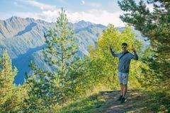 Un turista en pantalones cortos y una camiseta que se coloca encima de un acantilado en el fondo de árboles y que mira el hermoso Fotos de archivo