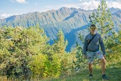Un turista en pantalones cortos y una camiseta que se coloca encima de un acantilado en el fondo de árboles y que mira el hermoso Imágenes de archivo libres de regalías