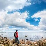 Un turista esamina la distanza su un fondo dell'orizzonte di mare immagini stock libere da diritti